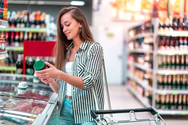 Jovem mulher com carrinho de compras escolhe, verificando o rótulo de produtos e comprando comida no supermercado