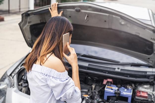 Jovem mulher com carro quebrado usando smartphone para assistência