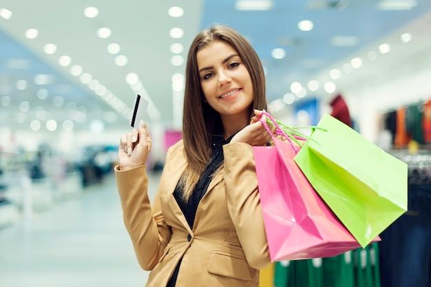 Jovem mulher com cartão de crédito e sacola de compras