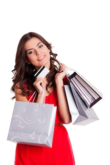 Jovem mulher com cartão de crédito e sacolas de compras