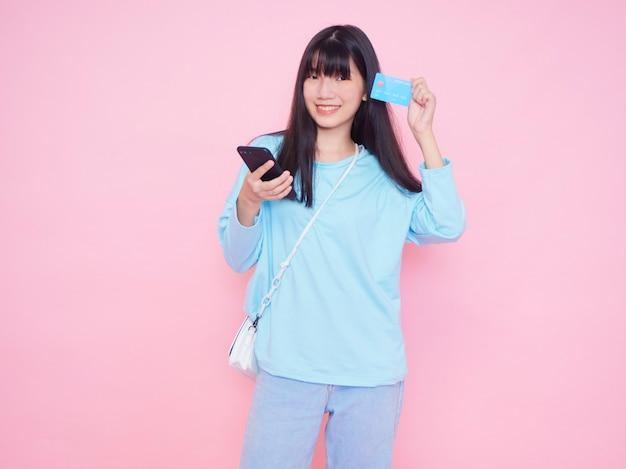 Jovem mulher com cartão de crédito e smartphone na parede rosa. compras online