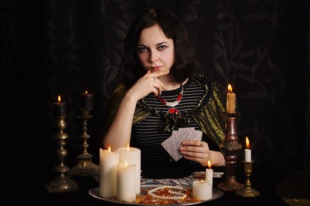Jovem mulher com cartas de adivinhação no quarto