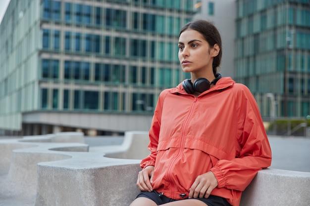 Jovem mulher com casaco de chuva inclina-se com os cotovelos na pedra faz exercícios ao ar livre, motiva a ter um estilo de vida saudável, entra para o esporte na rua da cidade olha para a frente poses contra um prédio urbano atrás