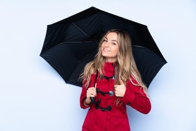 Jovem mulher com casaco de inverno e segurando um guarda-chuva com polegares para cima, porque algo de bom aconteceu