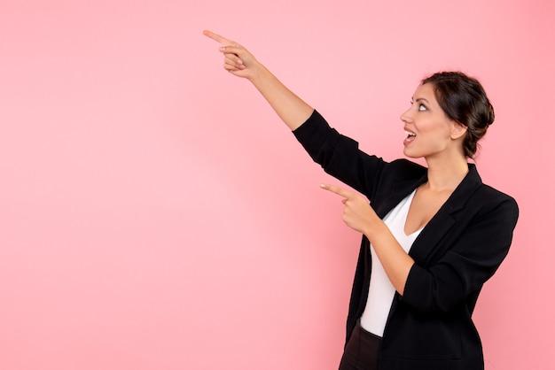 Jovem mulher com casaco escuro em fundo rosa