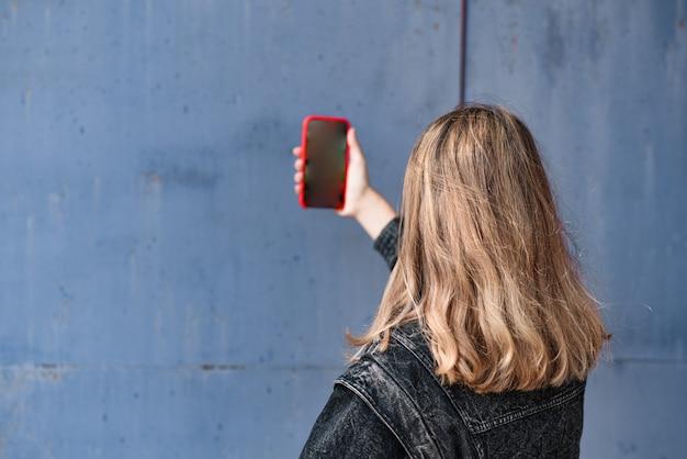 Jovem mulher com cauda longa e jaqueta jeans preta fotos ao telefone