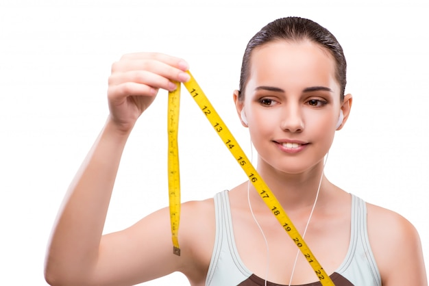 Jovem mulher com centímetro no conceito de dieta