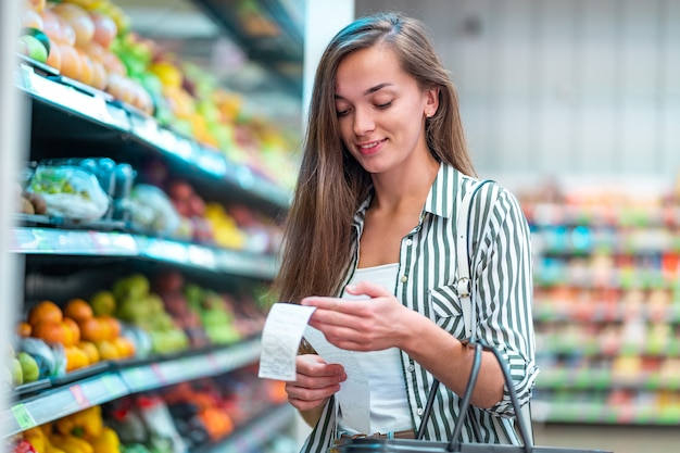 Jovem mulher com cesto de compras verifica e examina um recibo de venda após a compra de alimentos em uma mercearia
