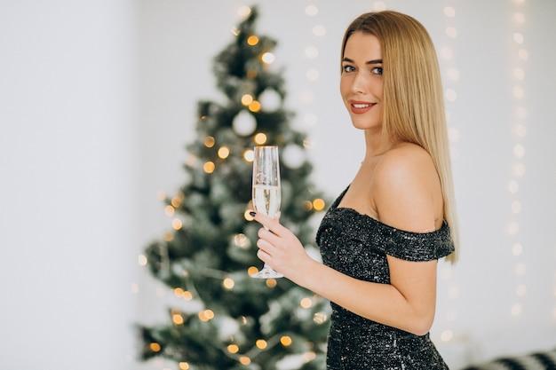 Jovem mulher com champanhe perto da árvore de natal