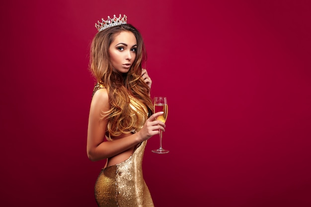 Jovem mulher com champanhe usando coroa e vestido dourado