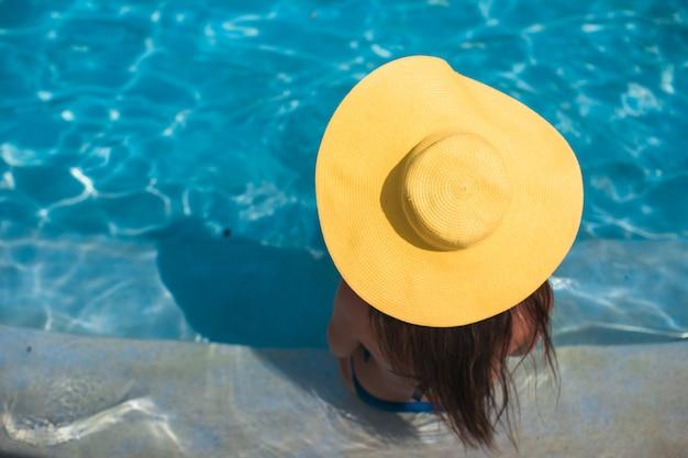 Jovem mulher com chapéu amarelo relaxante na piscina