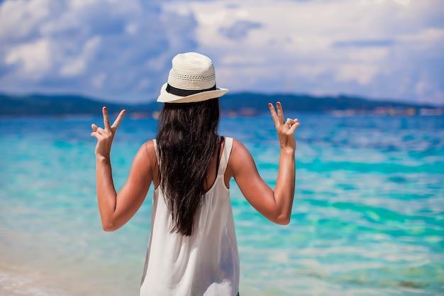 Jovem mulher com chapéu com as mãos levantadas na praia perfeita