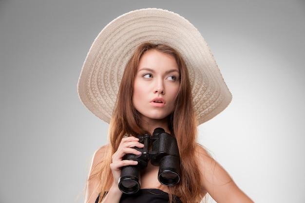 Jovem mulher com chapéu com binóculos