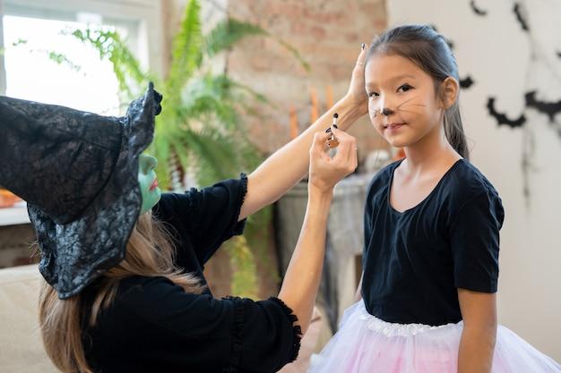 Jovem mulher com chapéu de bruxa e pulôver preto aplicando maquiagem de halloween no rosto da linda garota