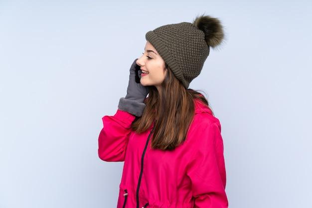 Jovem mulher com chapéu de inverno isolado na parede azul, mantendo uma conversa com o telefone móvel com alguém