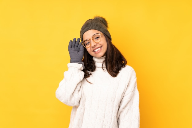 Jovem mulher com chapéu de inverno isolado parede amarela com óculos e feliz