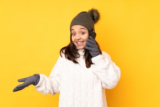 Jovem mulher com chapéu de inverno, mantendo uma conversa com o telefone móvel com alguém