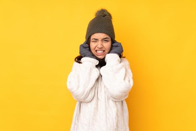 Jovem mulher com chapéu de inverno sobre parede amarela frustrado e cobrindo as orelhas