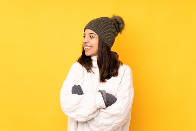 Jovem mulher com chapéu de inverno sobre parede amarela isolada feliz e sorridente