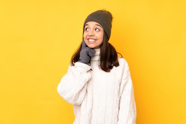 Jovem mulher com chapéu de inverno sobre parede amarela, pensando em uma idéia enquanto olha para cima