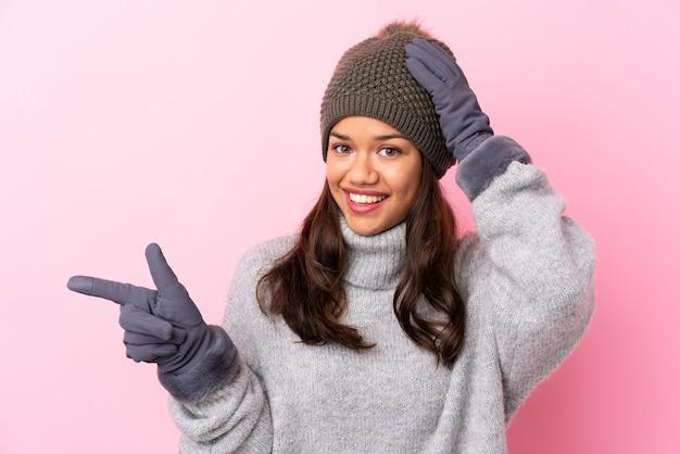 Jovem mulher com chapéu de inverno sobre parede isolada