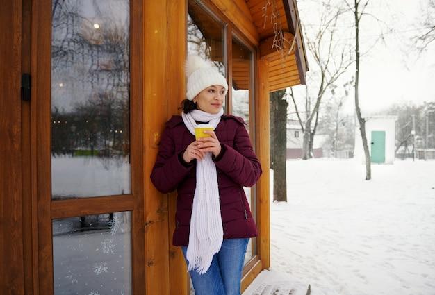 Jovem mulher com chapéu de malha de lã branca e cachecol, desfrutando de uma bebida quente durante o dia frio e gelado no parque.
