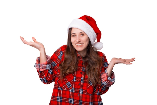 Jovem mulher com chapéu de natal está encolhendo os ombros sobre fundo branco.