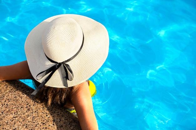 Jovem mulher com chapéu de palha amarelo descansando na piscina com água azul clara em dia ensolarado de verão