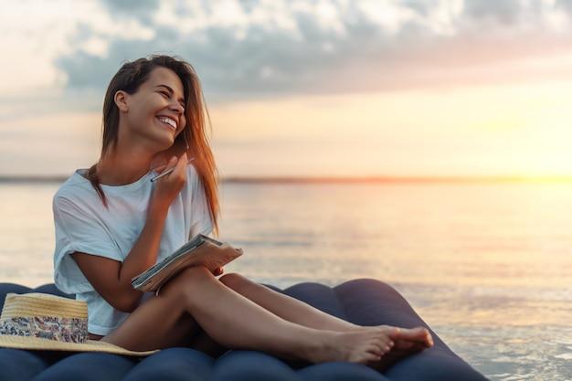 Jovem mulher com chapéu de palha, conversando com o smartphone e escrevendo na praia.