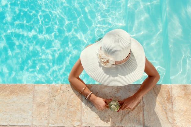 Jovem mulher com chapéu de palha e coquetel tropical fica na piscina