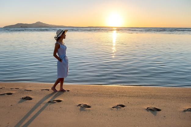 Jovem mulher com chapéu de palha e um vestido andando sozinha na praia de areia vazia na costa do mar do sol. garota solitária, olhando para o horizonte sobre a superfície calma do oceano em viagem de férias.