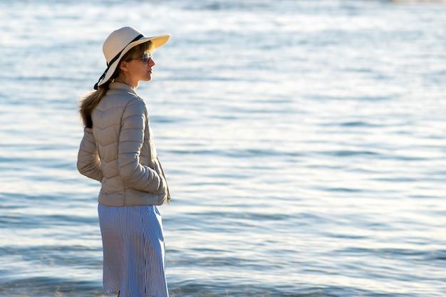 Jovem mulher com chapéu de palha e um vestido em pé sozinho na praia de areia vazia na beira-mar. garota de turista solitário, olhando o horizonte sobre a superfície do oceano calmo em viagem de férias.