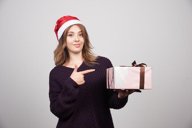 Jovem mulher com chapéu de papai noel, apontando para um presente.
