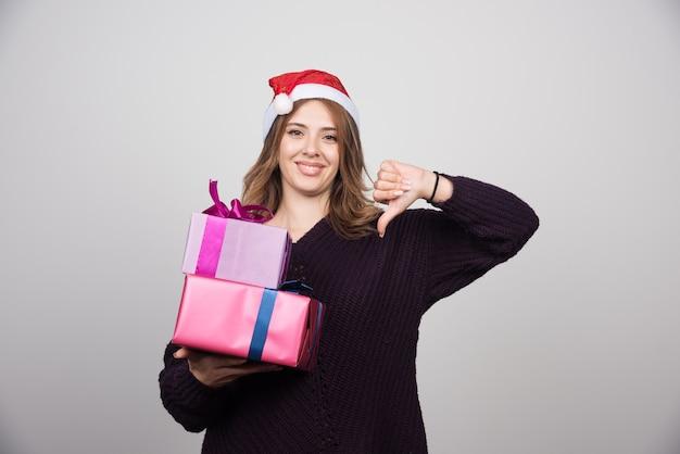 Jovem mulher com chapéu de papai noel com caixas de presente, mostrando um polegar para baixo.