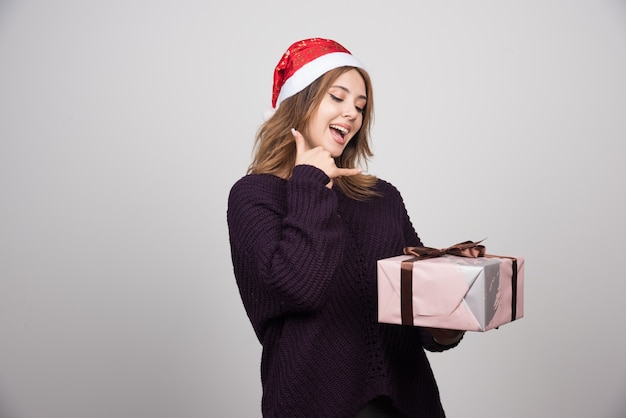Jovem mulher com chapéu de papai noel com um presente fazendo gesto de telefone com a mão e os dedos.