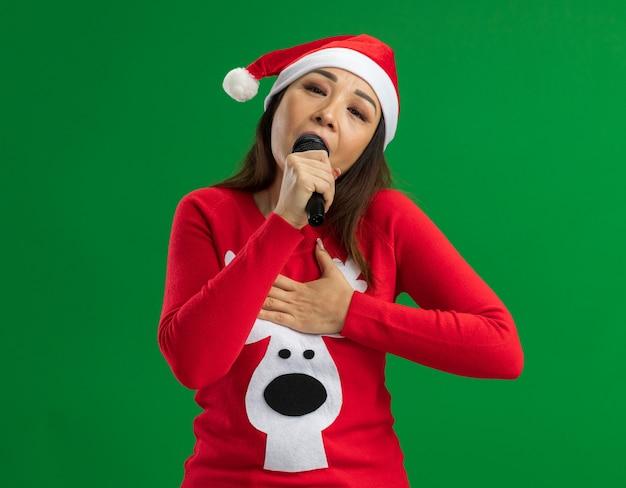 Jovem mulher com chapéu de papai noel de natal e suéter vermelho segurando a música e cantando, sentindo emoções positivas em pé sobre um fundo verde