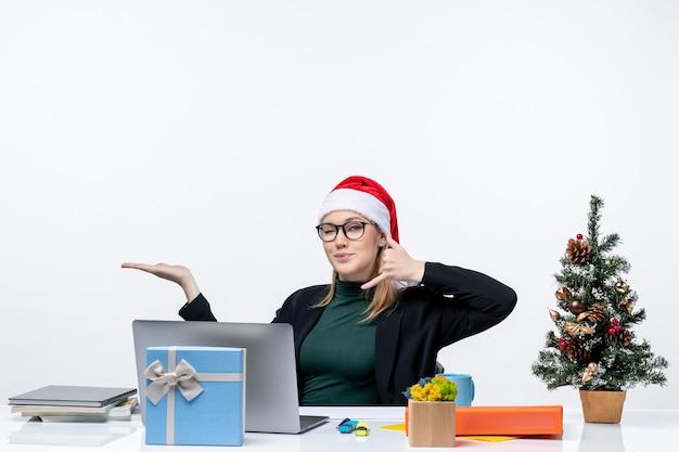 Jovem mulher com chapéu de papai noel e óculos, sentada à mesa com uma árvore de natal e um presente