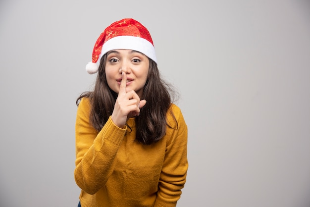 Jovem mulher com chapéu de papai noel fazendo sinal de silêncio.