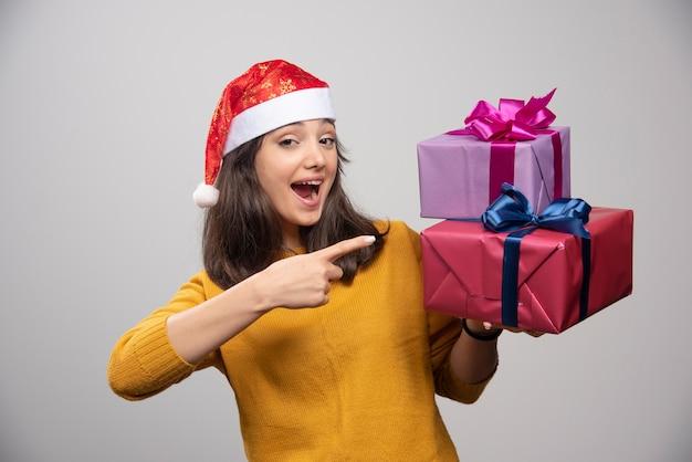 Jovem mulher com chapéu de papai noel mostrando os presentes de natal.