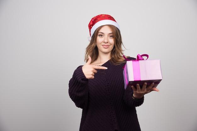Jovem mulher com chapéu de papai noel, mostrando uma caixa de presente presente.