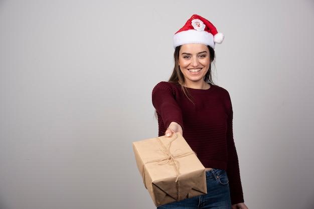 Jovem mulher com chapéu de papai noel, oferecendo o presente de natal em fundo cinza.
