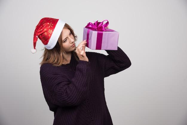 Jovem mulher com chapéu de papai noel, olhando para um presente de caixa de presente.