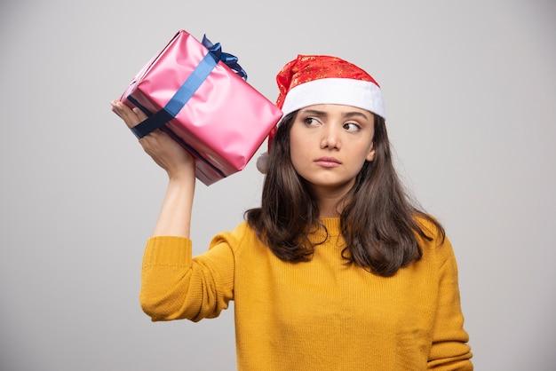 Jovem mulher com chapéu de papai noel segurando a caixa de presente.