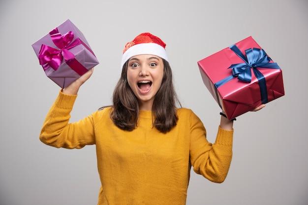 Jovem mulher com chapéu de papai noel segurando caixas de presente e se sentindo feliz.
