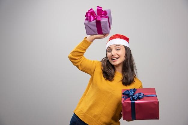 Jovem mulher com chapéu de papai noel segurando caixas de presente.