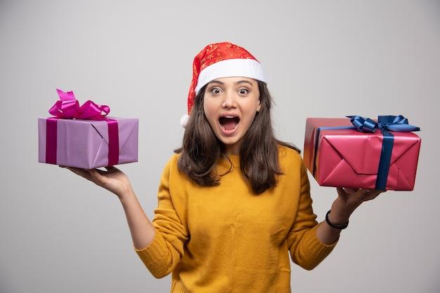 Jovem mulher com chapéu de papai noel segurando nas mãos os presentes de natal.