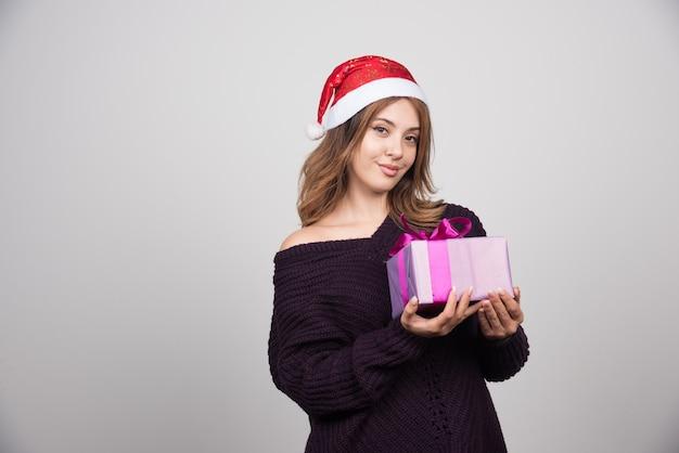Jovem mulher com chapéu de papai noel segurando uma caixa de presente presente.