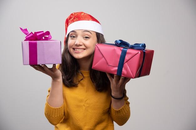 Jovem mulher com chapéu de papai noel vermelho com presentes de natal.