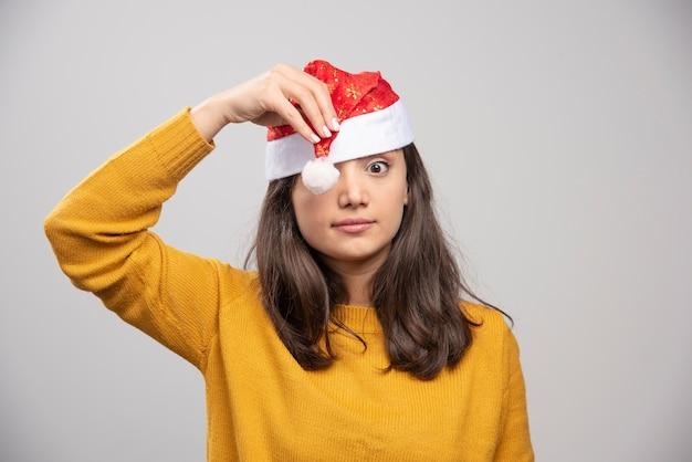 Jovem mulher com chapéu de papai noel vermelho posando sobre uma parede branca.