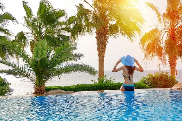 Jovem mulher com chapéu de verão senta-se à beira da piscina em viagens no mar.